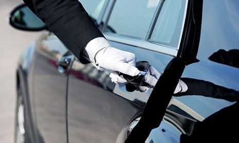 una mano con un guanto di velluto bianco sta aprendo la portiera di una macchina nera