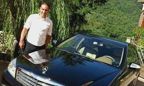 una macchina Mercedes di color blu vista da davanti e affianco un uomo con una camicia bianca e pantaloni neri