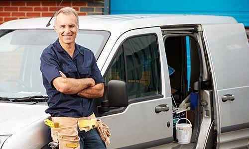 Idraulico in piedi accanto a un furgoncino
