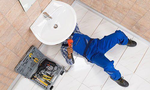 Idraulico che ripara lavandino in bagno