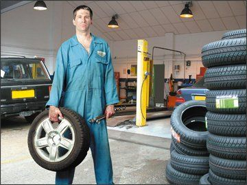 Man Holding A Tyre Next To A Stack Of Tyres