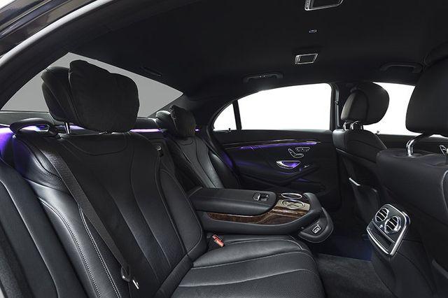 vista di un interno di un auto con sedili posteriori in pelle nera con bracciolo in mezzo e vista dei due sedili anteriori