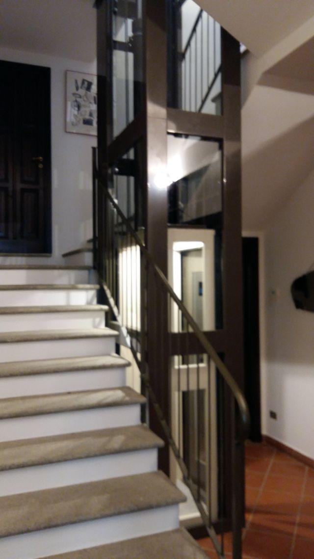 vista della porta di un ascensore esterna,accanto una porta finestra di una casa e sopra un balcone e una finestra con delle persiane marroni