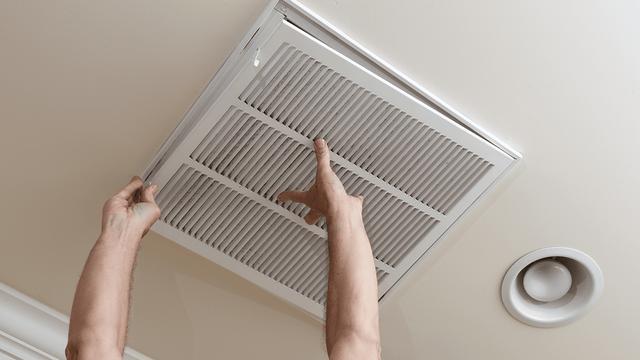 due mani che montano una griglia sul soffitto