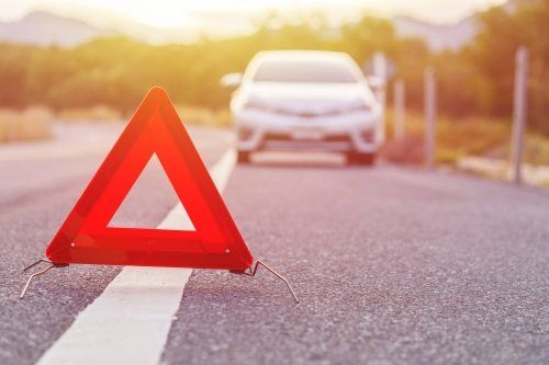 un triangolo d'emergenza e un'auto in panne