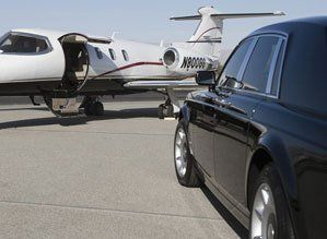 A black car beside a white private plane on the tarmac