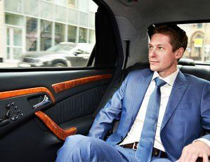A young man in a business suit, sitting in a taxi