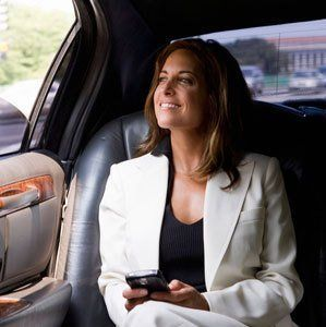 A young lady in a white suit, sitting in the back seat of a car