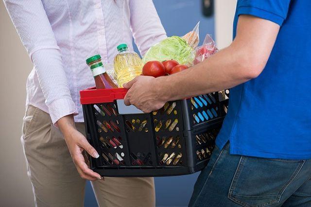 Un uomo mentre consegna un cestino di spesa a una donna