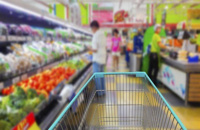 Un carrello per la spesa all'interno del supermercato con scaffali di prodotti su tutti due lati