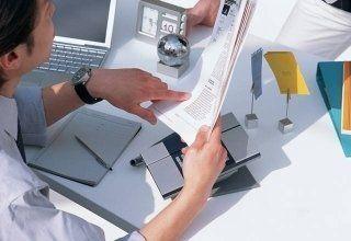 un uomo alla scrivania mentre controlla dei documenti