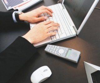 due mani che premono i tasti della tastiera di un portatile bianco