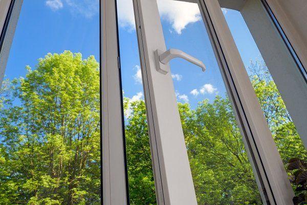una finestra bianca in pvc semi aperta e vista degli alberi con il cielo azzurro