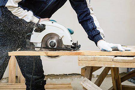 un falegname che taglia del legno con una sega elettrica