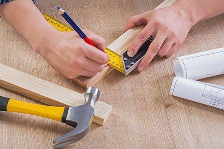 due mani con una matita delle piccole assi di legno e degli strumenti di misurzione