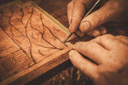 una mano che disegna su del legno