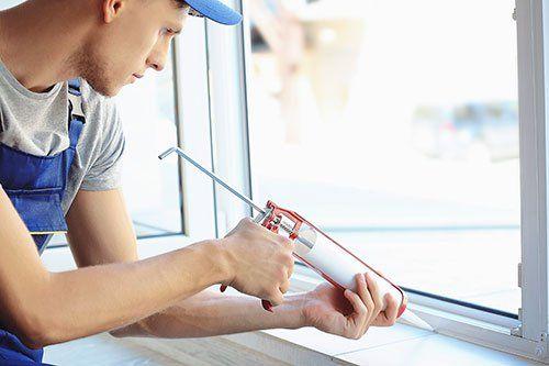 Operaio sigillando gli stipiti di una finestra a Varese