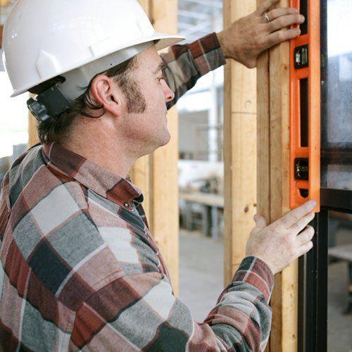 Operaio controllando livello di una finestra installata a Caronno Pertusella