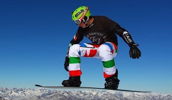 un ragazzo con casco verde, occhiali,maglietta nera e pantaloni in tema bandiera italiana durante un salto con lo snowboard visto lateralmente con lo sfondo detagne innevatelle mon