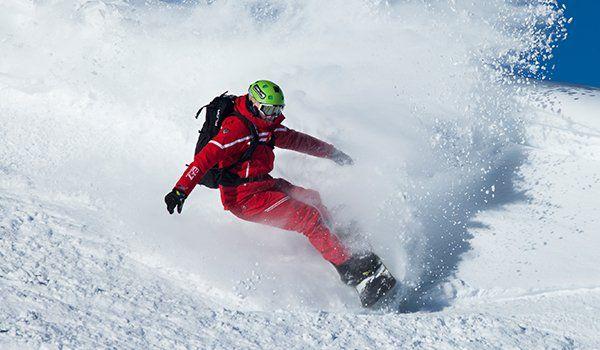 un uomo che si appresta a una discesa con lo snowboard e della neve che schizza