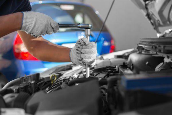 due mani con una chiave che avvita un bullone della zona motore di una macchina