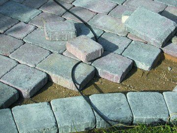 A close up of a driveway with bricks in the process of being laid