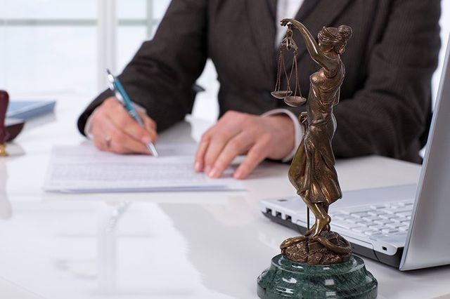 un uomo alla scrivania mentre scrive e una statuetta che impugna una bilancia a due piatti