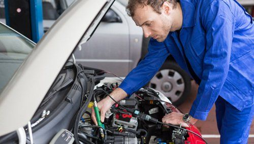 Professional testing the battery of a car