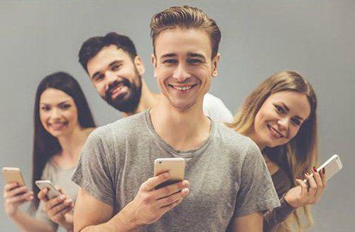 amici in fila indiana con un cellulare in mano