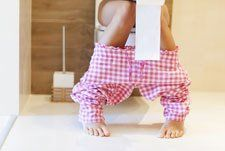 woman sitting on toilet with toilet paper in hand