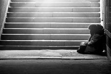Monochrome photo of homeless woman reading a book
