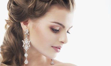 A lady with her hair in a half-updo, and long diamante earrings