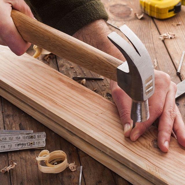 falegname mette un chiodo su asse di legno