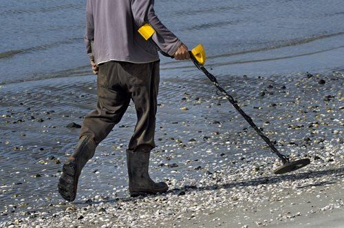 Man walking a bay with metal detector