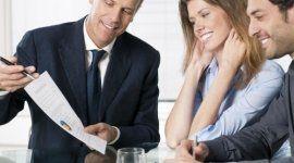 uomo vestito in abito formale mentre spiega quanto scritto in un documento a una coppia di persone