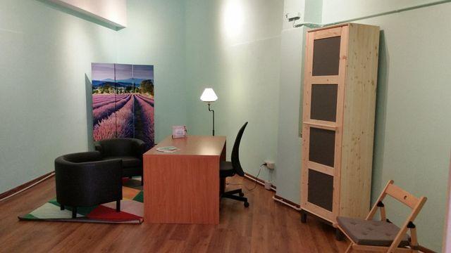 un ufficio con una scrivania, due poltrone e un mobile di legno