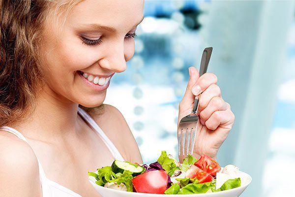 una donna con una coppa di insalata in mano