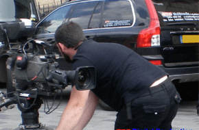 Camereman with professional camera filming a car
