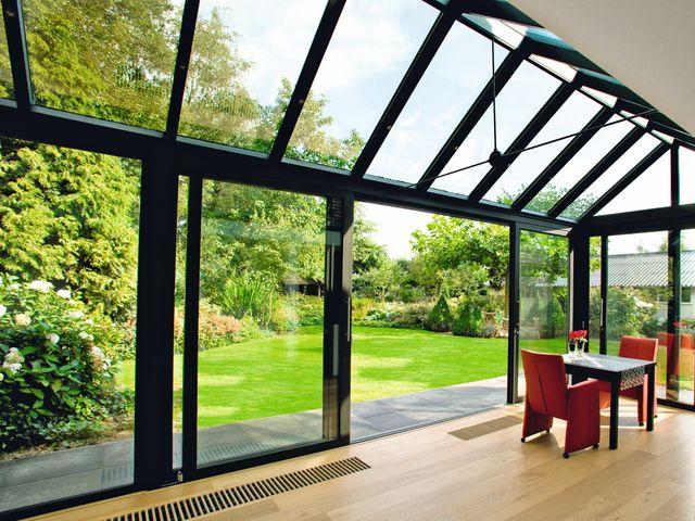 vista di una sedia all'interno di una casa con vetrate e vista del giardino e delle montagne