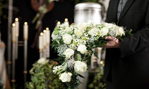Uomo portando un mazzo di fiori bianchi con delle candele nello sfondo.