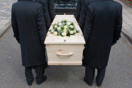 quattro becchini che mettono una bara dentro il carro funebre