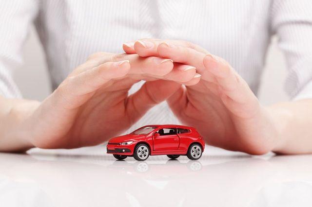 Due mani che coprono un modellino di una macchina rossa