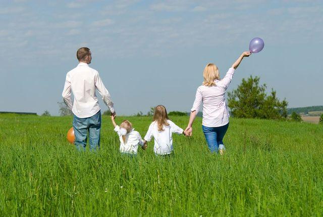Due bambine e dei genitori che tengono le loro mani in un prato verde