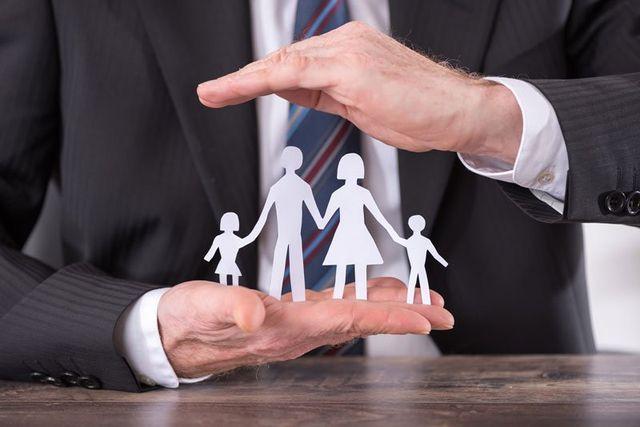 Due mani che coprono un modellino di una famiglia