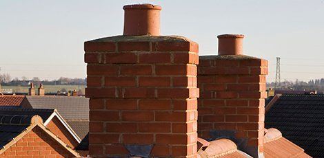 two chimneys with recent brickwork repairs