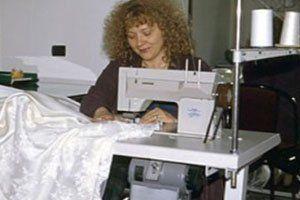 Una donna mentre cuce un abito di color bianco