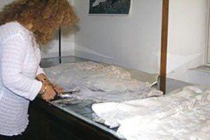 Una donna mentre taglia una stoffa di color bianco