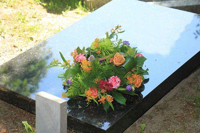 Semplice tomba di marmol nero coperta di fiori diverse in un angolo