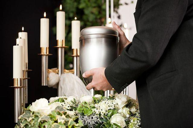 Presentazione di una delicata urna di metallo circondata di vele e sul manto di fiori bianche