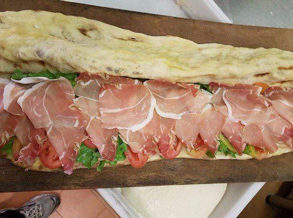 un pane lungo farcito con prosciutto crudo, insalata e pomodori